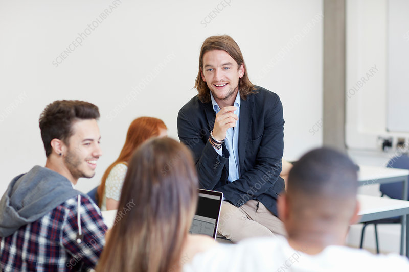 Male lecturer talking to students in classroom