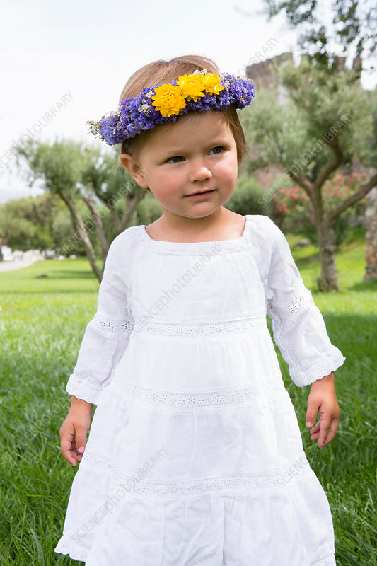 Female toddler in garden wearing floral headdress