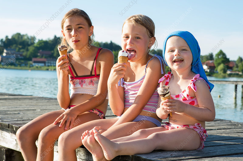 Two sisters and female toddler eating ice cream