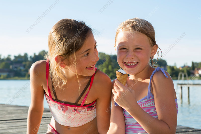 Two sisters on pier eating ice cream cones