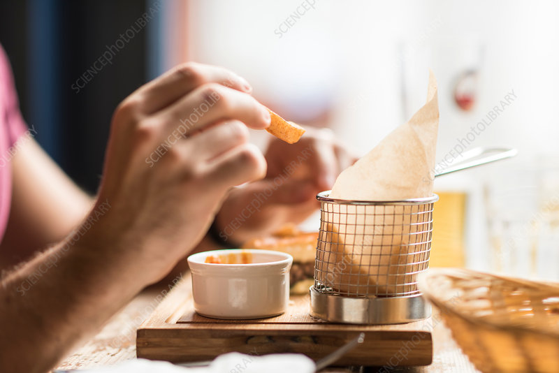 Hand of young man eating chips in restaurant