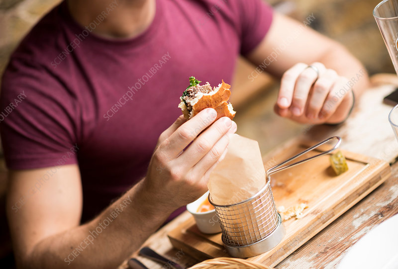 Young man eating burger in restaurant