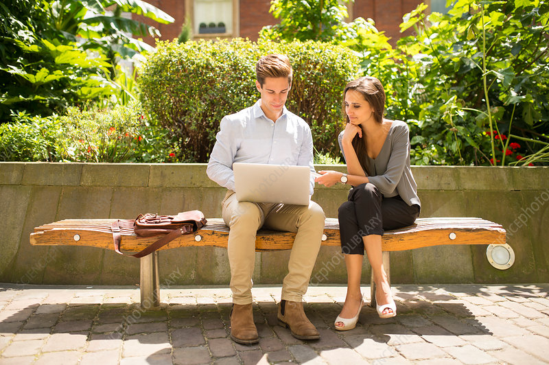 Businesswoman and man using laptop on bench