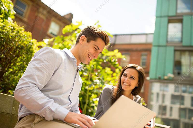 Businesswoman and man using laptop outside office