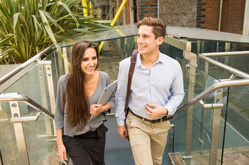 Businesswoman and man walking up stairway