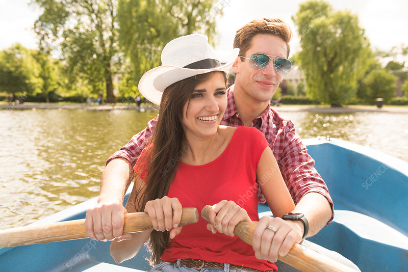 Happy young couple rowing a boat together