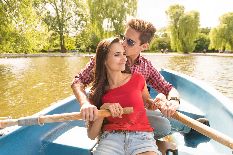 Romantic young couple rowing a boat together