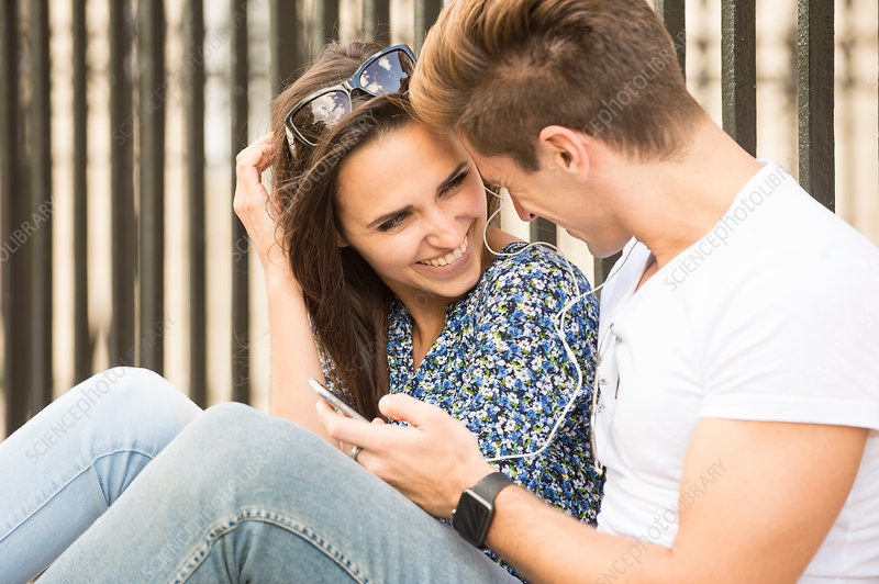 Happy young couple sitting on sidewalk