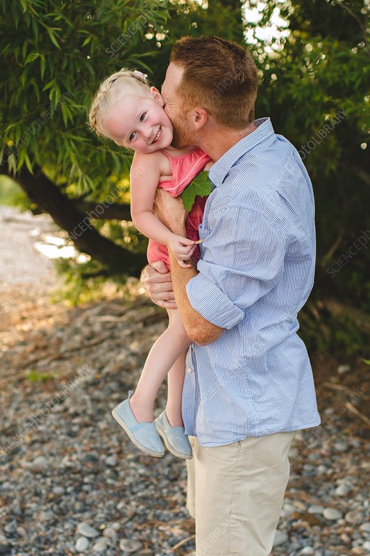 Mid adult man carrying and kissing daughter
