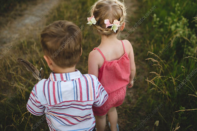 Girl and twin brother holding hands in meadow