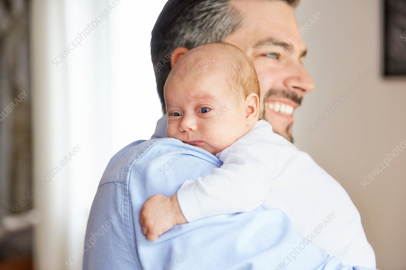 Man carrying baby daughter over his shoulder