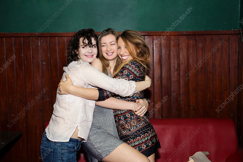 Female friends having group hug in bar