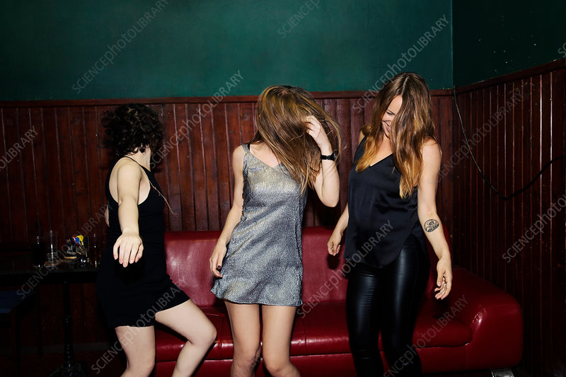 Female friends dancing in club on night