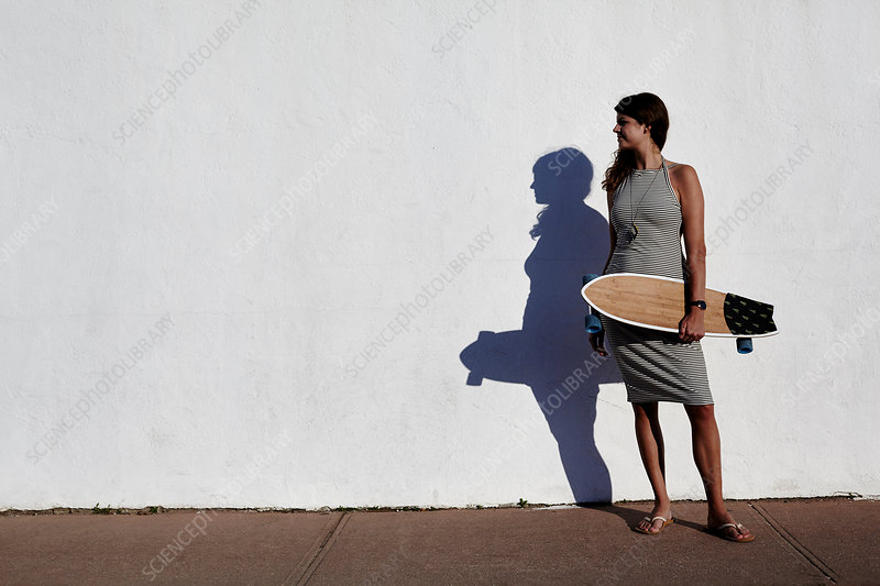 Young woman holding skateboard, New York, USA