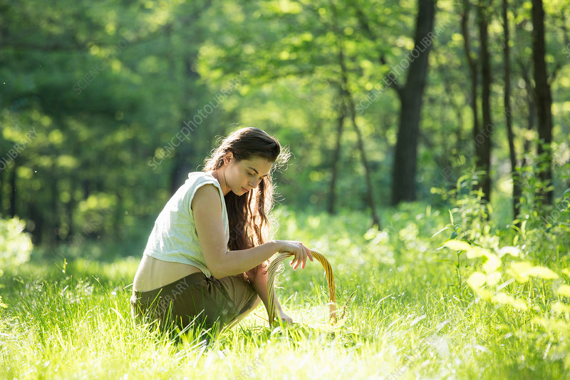 Woman crouching to forage wild herbs in forest