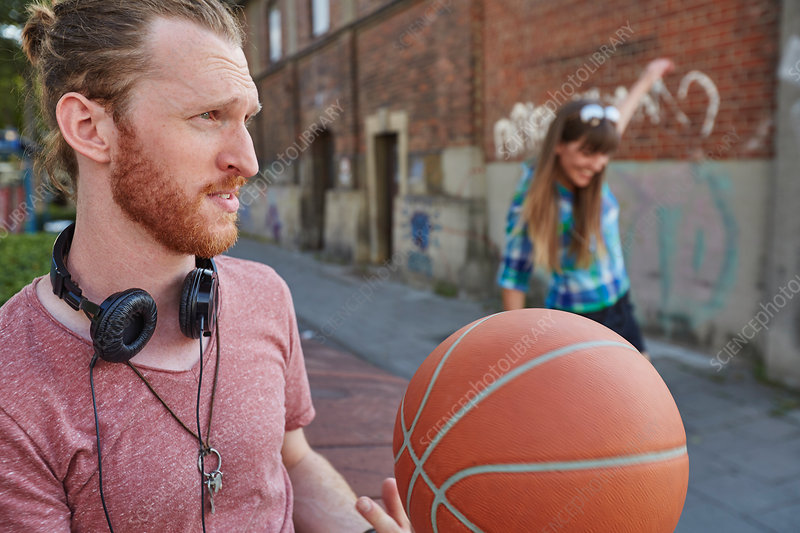 Couple outdoors, throwing basketball