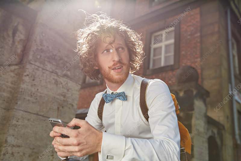 Man outdoors, using smartphone, wearing bow tie