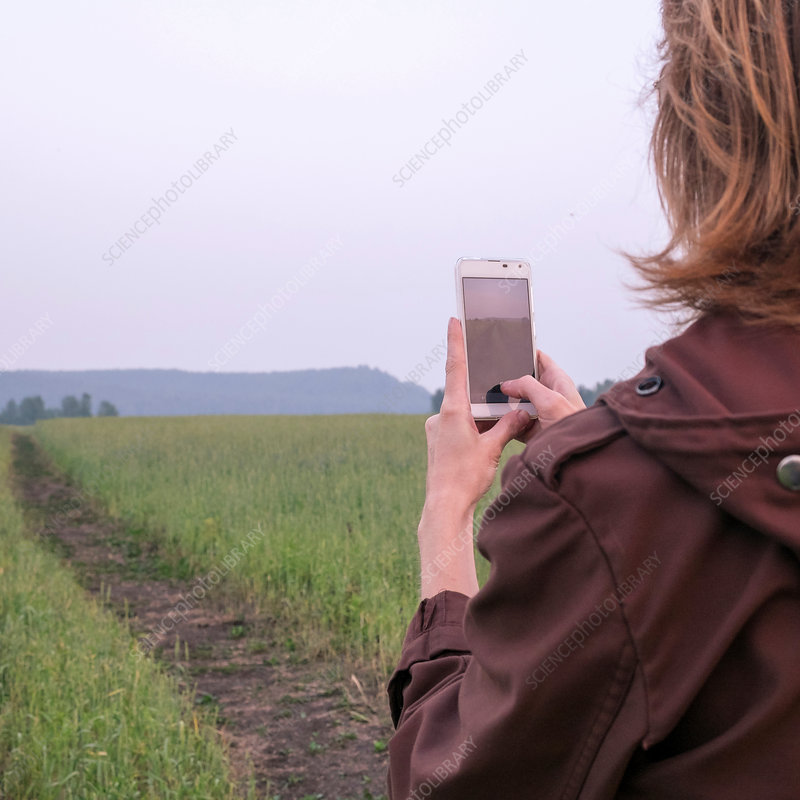 Woman standing in field photographing