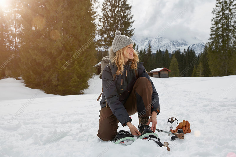 Woman putting on snow shoes in snowy landscape