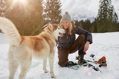 Woman crouching by beside dog in snowy landscape