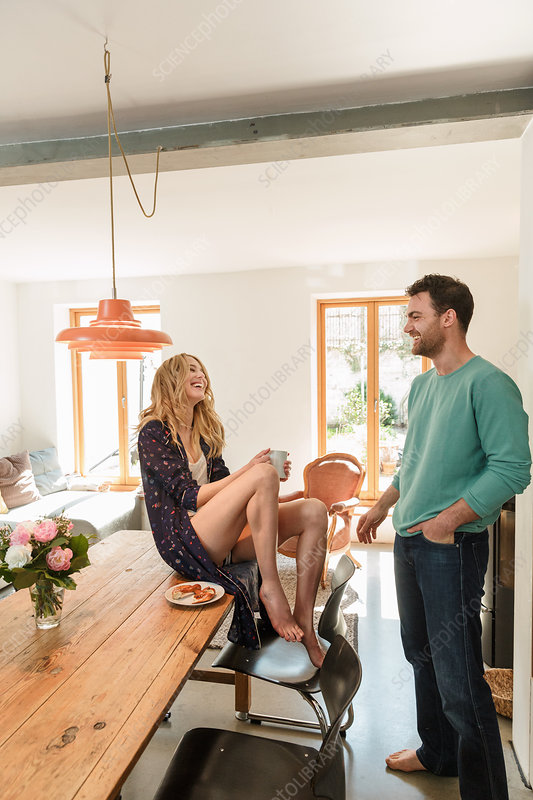 Couple in dining room sitting on table talking