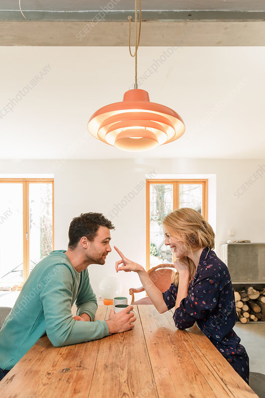 Couple face to face at dining table smiling