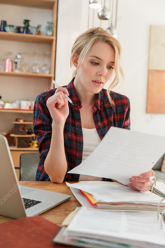 Woman with laptop looking at paperwork