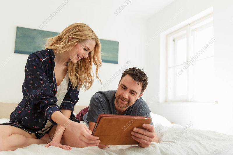 Couple on bed using digital tablet smiling