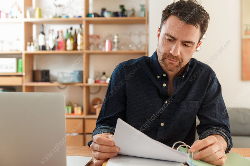 Man with laptop looking at paperwork