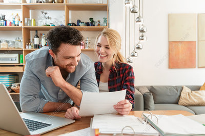 Couple with laptop looking at paperwork smiling