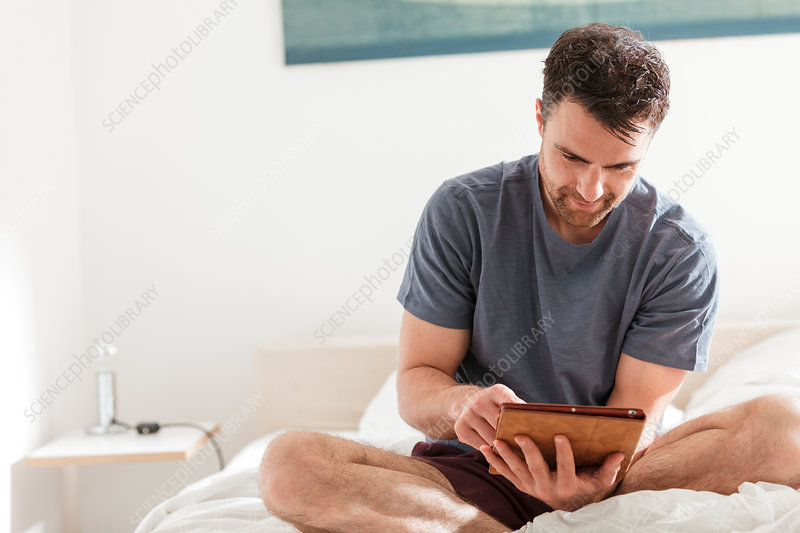Man sitting on bed using digital tablet