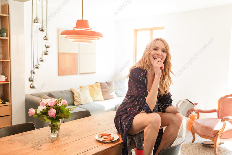 Woman on dining table holding mug smiling