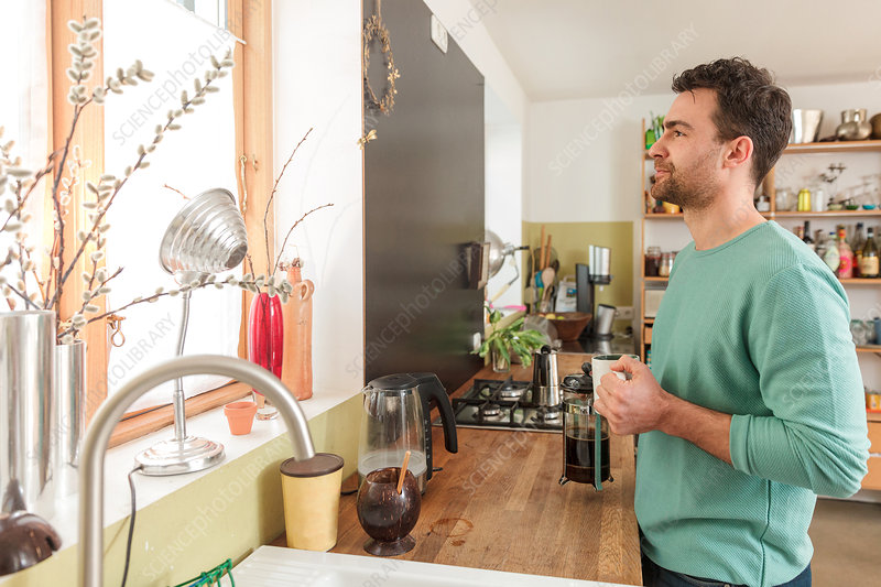Man in kitchen holding coffee cup