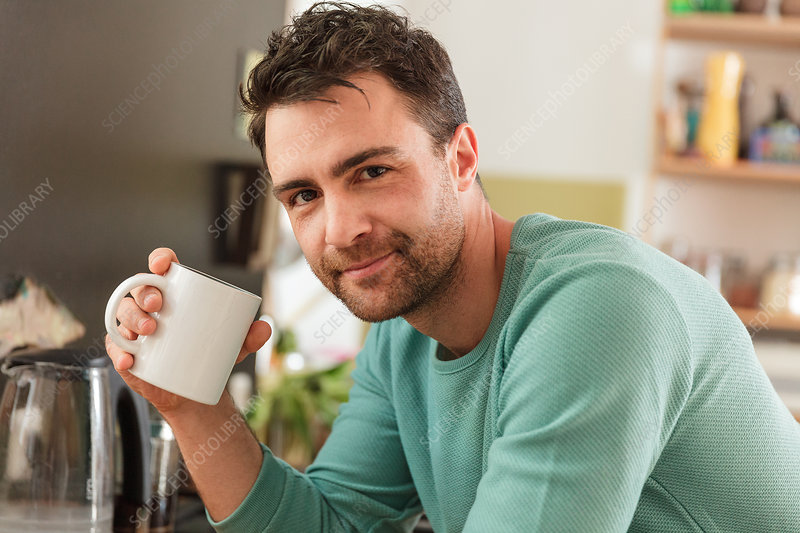 Man holding coffee cup smiling