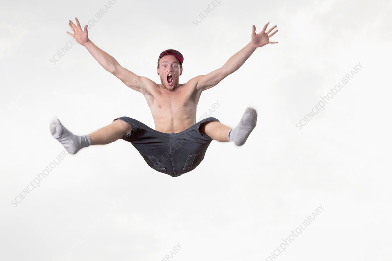 Bare chested man jumping in mid air