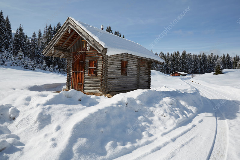 Log cabin on snow covered landscape