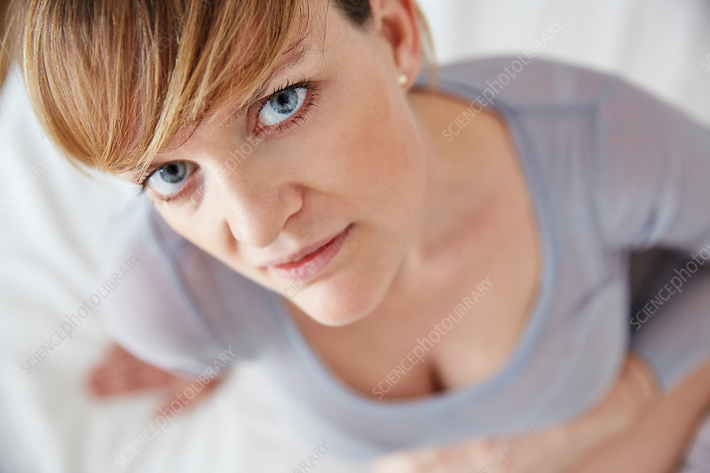 Woman sitting on bed, looking up at camera