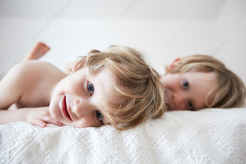 Boys lying on bed, smiling,