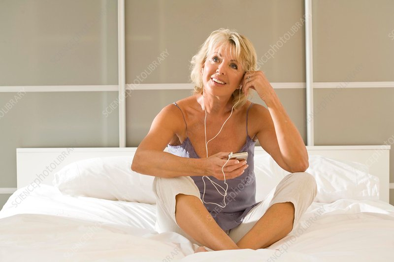 Woman sitting up in bed listening to earphones