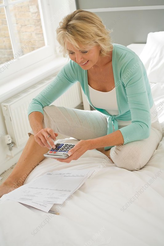 Woman sitting up on bed using calculator
