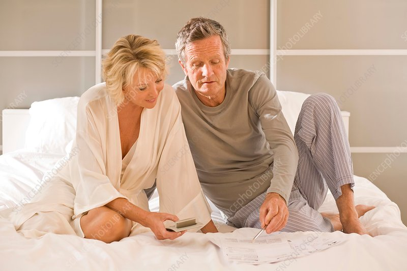 Couple sitting up on bed using calculator