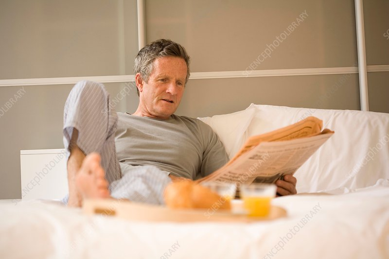 Senior man sitting up in bed reading newspaper