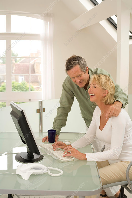 Couple using computer and laughing at home desk
