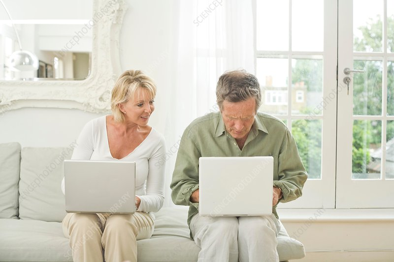 Couple on sofa using laptops