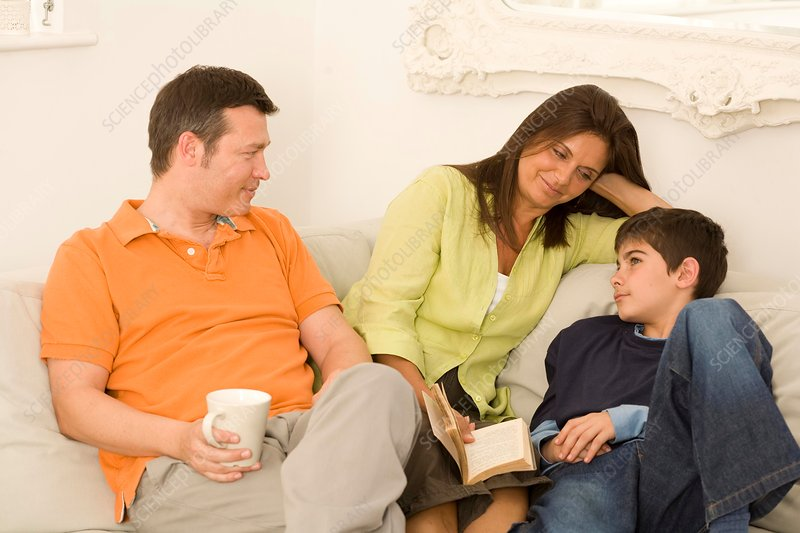 Mature couple and son chatting on sofa