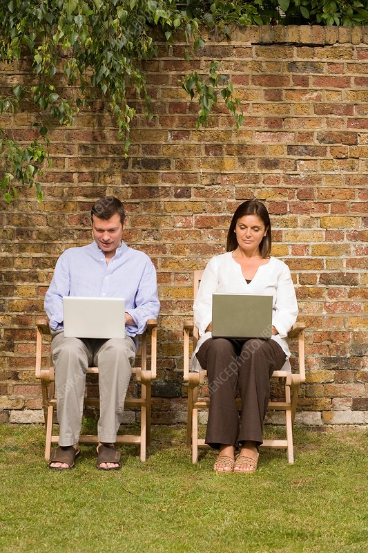 Mature couple sitting in garden using laptops