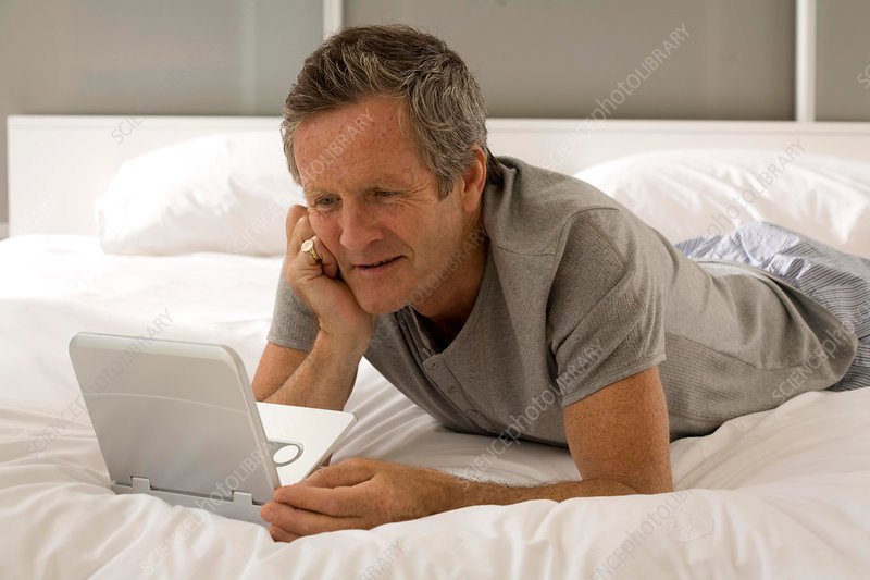Puzzled senior man lying on bed staring at laptop