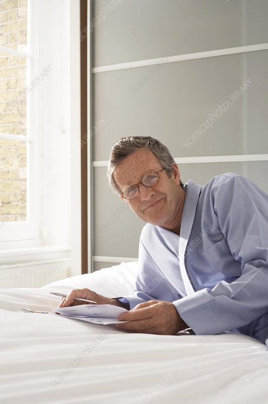 Senior man reclining on bed doing paperwork