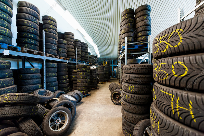 Rows of stacked tyres in repair garage warehouse