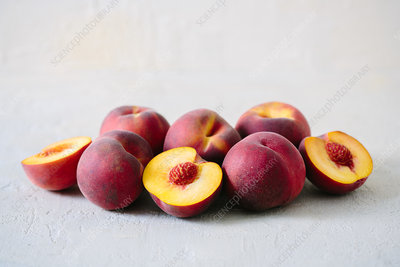 Whole and half peaches on table